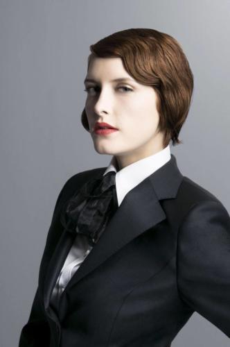 51 Vrouwelijk colbert op maat gemaakt van zwarte gllanzende wol met bijpassende maatblouse