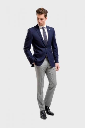 900 Helder blauwe blazer met opgestikte zakken en smalle revers. Slank gesneden broek met bijpassend maathemd
