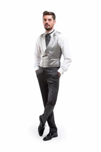 Gilet jacquet gemaakt van feestelijk glanzende zijde met sjaalkraag en zijde beklede knopen. Opgesneden revers en donkergrijze rug met riempje voor extra taille