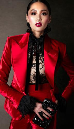Rode velourse damessmoking gemaakt met brede revers en hoge broek