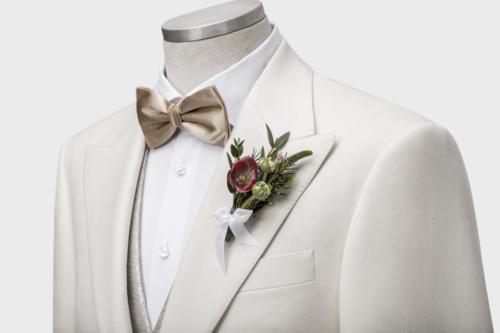 Wit trouwkostuum gemaakt met glanzend vest en goudkleurige strik